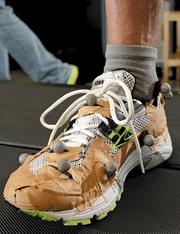 Motion caption targets on a Brooks Ravenna shoe that volunteer tester Eric Ott in the Brooks Sports Human Performance Lab. The shoe is covered in brown tape to cover any reflective surfaces that would interfere with the motion capture.