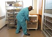Matt Harvey, unit coordinator for Central Services,  restocks a supplies cart in the new emergency department at Virginia Mason Medical Center. Every treatment room has a cart with supplies — and every cart is set up the same way.