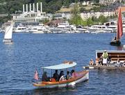 Sightseers return from a free cruise aboard Dora, a 23-foot electric launch characteristic of the early 1900s, at Lake Union's  Center for Wooden Boats. The center seen a near-doubling of attendance at its annual July festival.