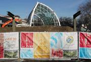 The Chihuly Garden and Glass exhibit rises behind a wall displaying posters of the Seattle World's Fair's golden anniversary celebrations. The Chihuly exhibit opens this spring.