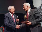 Broadcast journalist Dan Rather (left) presents an award to Washington State University communications professor Glenn Johnson.