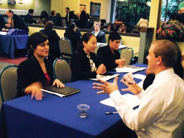Recent BankWorks graduates Monica Cardenas (from left), Jing Qing Fan and Mona McDermott interview with bankers for teller jobs. Their interviews took place at North Seattle Community College on graduation day.
