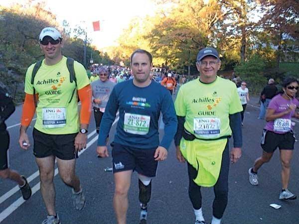 Mercer Island executive Bob Cremin (right) and an unidentified volunteer help guide war veteran Matt Fisher (center) through the New York City Marathon.