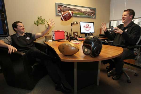 Explore Consulting partners Steve Jones, CEO (left) and Jeremy DeSpain, COO toss a football in their Bellevue offices.