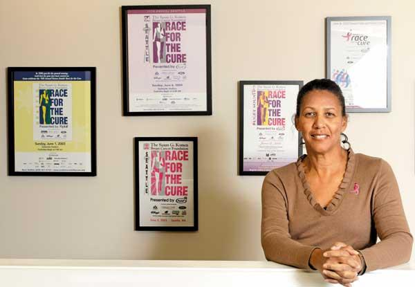 Cheryl Shaw, executive director of the Puget Sound affiliate of Susan G. Komen for the Cure, displays Race for the Cure posters from previous years in the group's office. In the wake of the Planned Parenthood controversy, the number of people registering to take part in this year's race is down 42 percent.