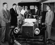 "In this photo from the late 1950s to early 1960s, James ""Jim"" W. Will (second from left) stands with Leon Titus Sr. behind the steering wheel of a 1906 Ford Model N, with Paul Titus in the passenger seat. In 1938, Leon Titus Sr. opened a Ford franchise in Tacoma. Shortly afterward James Will and Titus became business partners."