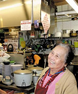 Mila Apostol of Oriental Mart at Pike Place Market smiles as she talks about the new ventilation hood (top left) installed during the market renovation. During the construction period, however, her sales shrank to a fraction of the normal level and Apostol left for the Philippines.