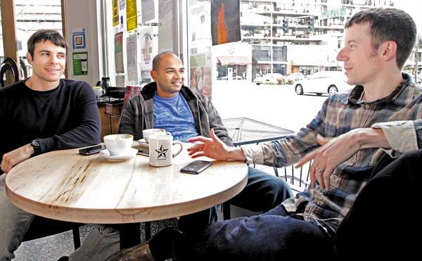 Audiogalaxy founders Michael Merhej (from left), Viraj Mody and Tom Kleinpeter hold a staff meeting at Zoka Coffee in Kirkland. They usually work on their music-streaming startup from their homes, but once or twice a week they gather at a coffee shop.