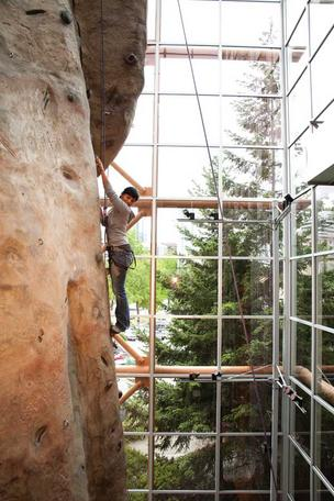 REI customer Ana Gonzalez climbs Pinnacle, REI's famous climbing wall inside its flagship store in Seattle.