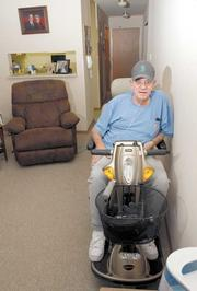 George Yilek parks his scooter along the wall of his living room to charge.