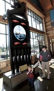 """SENSE OF PLACE: Jennifer Zill and her son Kellan stand by an artwork  called """"Sudhubs,"""" or Snohomish People, by artist James Madison."""