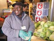 Volunteer Magnus Moseray, an immigrant from West Africa, laughs while portioning cabbage at the Rainier Valley Food Bank. The Seattle charity has benefitted from an upsurge of volunteer activity.