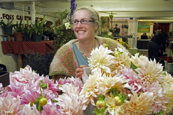 Diane Szukovathy, president of the Seattle Wholesale Growers Market, displays her own farm's dahlias at the bustling Wednesday morning sale.