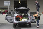 """Diane Larson of Mercer Island Florist loads flowers into her car at the Seattle Wholesale Growers Market. """"This is the most exciting thing that has happened in flower buying in 50 years,"""" she said."""