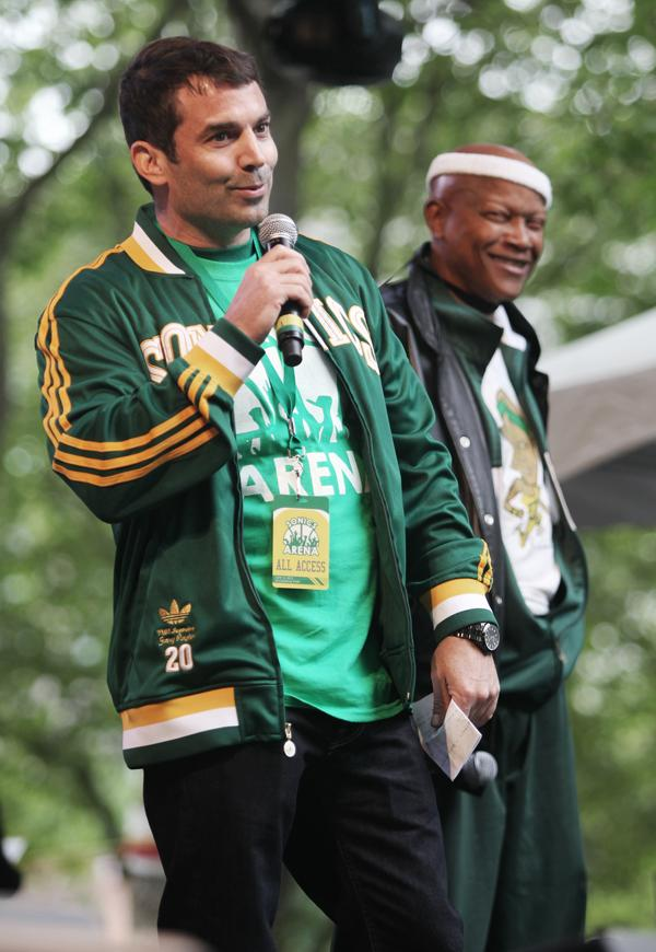 """Proposed NBA/NHL sports arena investor Chris Hansen, left, speaks to thousands of """"Bring back the Sonics"""" fans while legendary retired Seattle SuperSonics star Slick Watts stands nearby during a rally at Occidental Park in Seattle on Thursday."""
