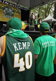 """""""Bring back the Sonics"""" fans Kurtis Manke (left) and Brian McElroy join thousands at a rally at Occidental Park in Seattle on Thursday."""