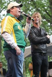 """Former Guns N' Roses bass player Duff McKagan, a Seattle native, right, listens while Seattle sports radio show host Mike Gastineau fires up the crowd of thousands of sports fans who flocked to Occidental Park in Seattle's Pioneer Square to attend a """"Bring back the Sonics"""" rally Thursday. Earlier, McKagan urged the crowd to tweet members of the Seattle City Council and King County Council to show support for bringing an NBA team back to Seattle."""