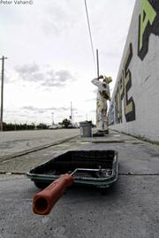 Graffiti artist Above takes a break from painting his political installation in Wynwood.