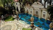 The Versace emblem next to the mosaic pool, which is lined in 24-karat gold.