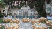 Tables arranged for an event in the courtyard next to the mosaic pool.