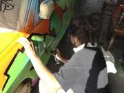 An artist spray paints a car that is being turned into a work of art at Rolling Stock.