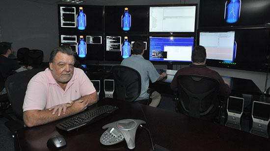 Hank Asher sits in the command center for his business.