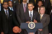 LeBron James and Heat owner Micky Arison flank the president.