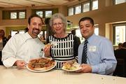 Broward County Commissioner Sue Gunzburger, center, poses with California Pizza Kitchen Chef Brian Sullivan, senior VP of Culinary Innovation, and a guest during the preview of the restaurant's new location at Sawgrass Mills Mall.