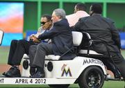 Muhammad Ali and Jeffrey Loria ride onto the field.