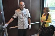 Amado Luis operates one of the elevators for Flory Miranda. These attendants assist patients and help ensure they get to the right location.