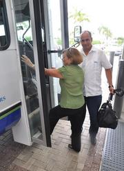 Flory Miranda boards the bus to go home with driver Carlos Rodriguez.
