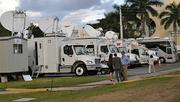 Dozens of news satellite trucks line a parking lot behind the debate hall on Oct. 22.