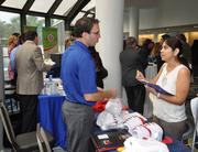 Jason Birn of One Beat CPR talks to Uttma Dham of Westside Dental Center at the health fair.