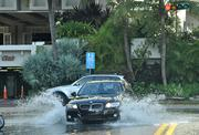 A car drives through the water in front of South Bay Club on flooded West Avenue on Miami Beach.
