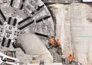Operators crawl out of the tunnel boring machine.