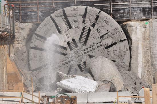 The cutter head of the boring machine is still spinning and pouring out water as it completes its breakthrough.
