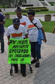 "Protestors Juanita Alvarez, Herminia Nasser and Jose Moutaner, whose sign reads: ""One Miami presents support for fair wages for workers."""