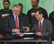 Heat President Pat Riley receives a beer wagon sculpture from Mingbo Sun, president of Tsingtao Brewery Co.