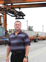 A mobile crane lifts containers from trucks to trains and towers over Kevin Little, an assistant GM at the FEC's Hialeah rail yard.