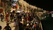 Crowds sit along the riverfront of the Valletta Waterfront promenade in Malta.