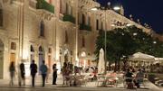People visit outdoor cafes along the Valletta Waterfront in Malta.