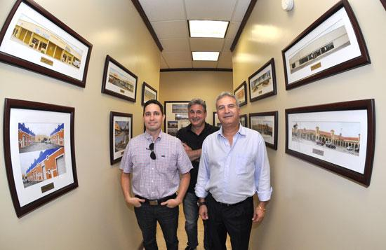 Carlos Segrera, non-operating partner Alan Lipton and Yoram Izhak with photographs of some of I.M.C. Property Management's properties.