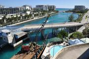 A crane builds a 200-foot dock near the pool. The Atlantic Ocean is in the distance.