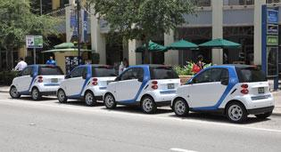 Several of Car2Go's fleet of Smart ForTwo vehicles are lined up at Mary Brickell Village in Miami.