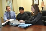 Attorneys Thomas Ice, left,  and Amanda Lundergan, right, consult with client Roman Pino.