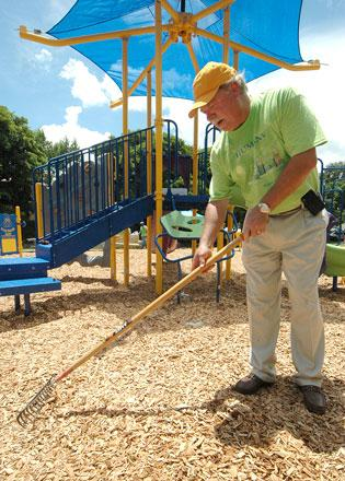Humana CEO Mike McCallister raked mulch at the multigenerational playground it donated to the city of Lauderhill.