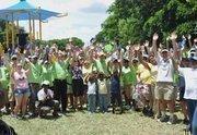 Volunteers cheer as the Humana multigenerational playground opens.