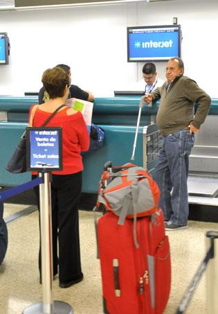 Interjet customer service agent Ronald Frixione assists passengers in Miami.