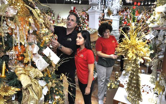 The Christmas Palace owner Jimmy Knips arranges decorations with temporary employees Danay Quesada and Susana Perea at the Hialeah location.