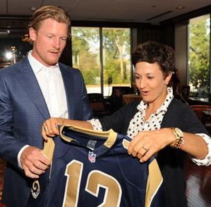 Annie Castellano, creative director at Switch, received a St. Louis Rams jersey from Rams General Manager Les Snead. Castellano is a winner of the St. Louis Business Journal's Most Influential Women in Business (MIBW).